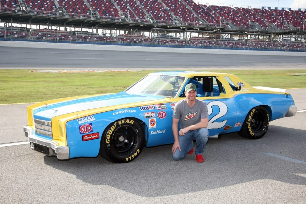 Dale Earnhardt Jr. poses by the car his father drove in 1980. (Michael Tomberlin / Alabama NewsCenter)