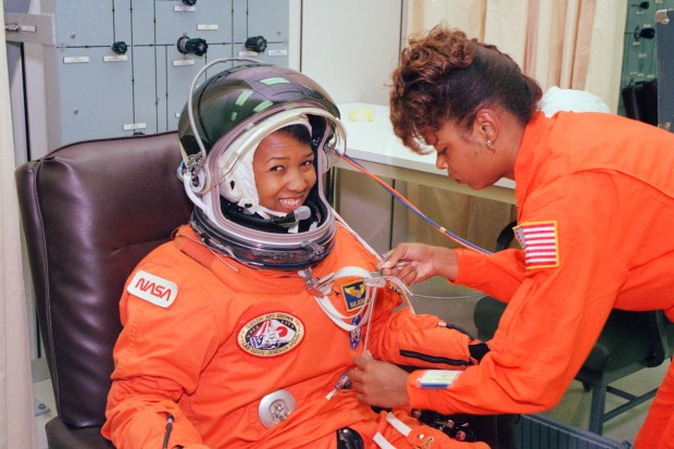 "On Sept. 12, 1992, launch day of the STS-47 Spacelab-J mission on space shuttle Endeavour, NASA astronaut Mae Jemison waits as her suit technician, Sharon McDougle, performs a unpressurized and pressurized leak check on her spacesuit at the Operations and Checkout Building at Kennedy Space Center. Dr. Jemison was the science mission specialist on the eight-day joint mission with Japan's space agency, which included 24 materials science and 20 life sciences experiments. She was the first African-American woman to fly in space. McDougle said of her role as Dr. Jemison's suit tech, ""I just wanted it to be a good experience for her. I'm sure it was probably a little scary for her being the first African-American woman to go into space, so I wanted to do my part in making it special for her too. And for me, because I was excited about being a part of history."" (Image credit: NASA)"