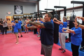 Gym owner Chris Wheeles leads the class in stretches. (Karim Shamsi-Basha / Alabama NewsCenter)