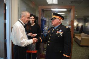 Retired Capt. Rose is congratulated by Command Historian Claus Martel. (Karim Shamshi-Basha/Alabama NewsCenter)