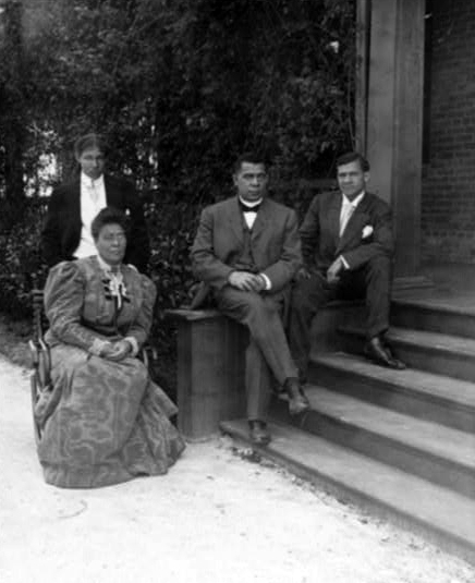 Booker T. Washington, seated on steps of porch, with wife and two sons, c. 1906. (Stereograph by Underwood & Underwood, Library of Congress Prints and Photographs Division)