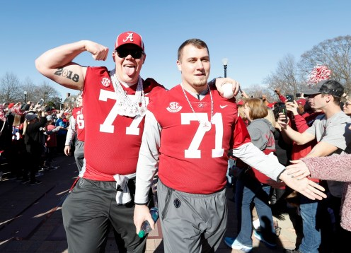 Alabama offensive linemen Matt Womack (77) and Ross Pierschbacher (71) celebrate with fans. (Amelia B. Barton)