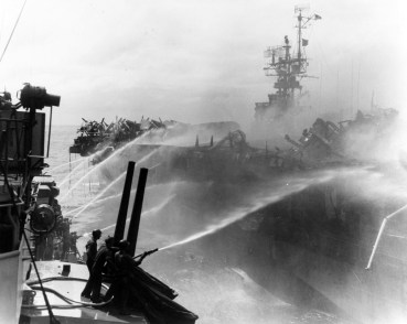 Crewmen on USS Birmingham (CL-62) play fire hoses on the burning USS Princeton (CVL-23), as their ship comes alongside to assist in damage control measures on Oct. 24, 1944. (Catalog #: 80-G-270357, Archives Branch, Naval History and Heritage Command, Washington, DC)