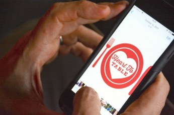Marco Morosini checks the Heart to Table logo on his phone. (Karim Shamsi-Basha / Alabama NewsCenter)