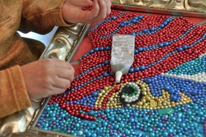 It takes a lot of Mardi Gras beads to make one of McCarron's paintings, and it takes hours to cut the necklaces apart. (Karim Shamsi-Basha / Alabama NewsCenter)