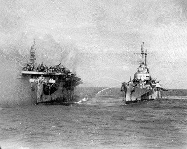 USS Birmingham (CL-62) comes alongside the burning USS Princeton (CVL-23) to assist with fire-fighting, Oct. 24, 1944. (Photograph by the U.S. Navy, NARA, Wikipedia)