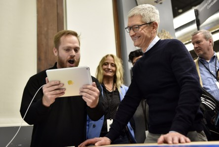 Tim Cook, chief executive officer of Apple Inc., right, smiles while speaking with an attendee while touring a technology lab during an event at Lane Technical College Prep High School in Chicago. (Christopher Dilts/Bloomberg)