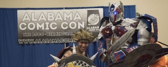 Two superheroes pose at the Alabama Comic Con sign. (Brittany Faush / Alabama NewsCenter)