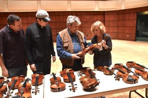 Avshi Weinstein, Alabama Symphony Conductor Carlos Izcaray, Amnon Weinstein and Marilyn Pipkin examine the Violins of Hope at the Alys Stephens Center. (Karim Shamsi-Basha/Alabama NewsCenter)