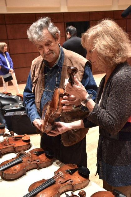 Amnon Weinstein shows a violin to Marilyn Pipkin. (Karim Shamsi-Basha/Alabama NewsCenter)