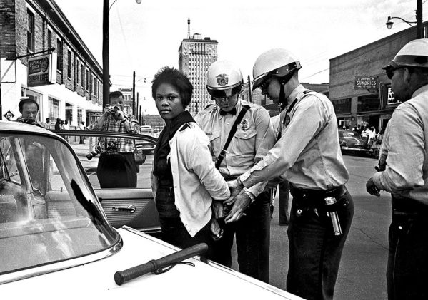 Birmingham police arrest Parker High School student Mattie Howard in front of the Carver Theatre on the sixth day of the Children's Crusade in May 1963. (From Encyclopedia of Alabama, photograph by Norman Dean, photo courtesy of The Birmingham News)
