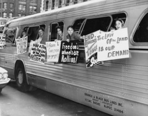 Freedom Riders hang anti-segregation signs from bus windows. In the early 1960s, the Congress of Racial Equality, an integrated group that promoted nonviolent methods to achieve racial equality, sent members to ride on public buses and trains to protest segregation of transportation networks. (Library of Congress, U.S. Embassy, The Hague, Flickr)