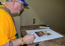 A veteran signs the memory poster. (Donna Cope/Alabama NewsCenter)