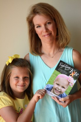 "Kate and Erin Miller with a copy of ""Fighting for Kate,"" the story of Kate's successful battle with childhood leukemia. (Karim Shamsi-Basha/Alabama NewsCenter)"