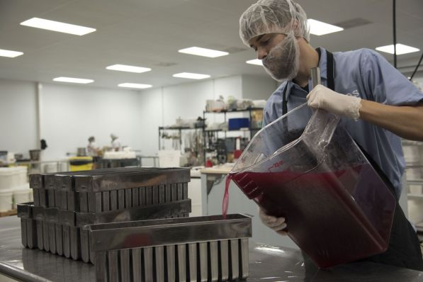 An employee pours the real fruit mixture into molds. (Brittany Faush/Alabama NewsCenter)