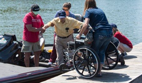 Navy veteran Hubert Craft is assisted exiting a boat after a day on Lake Logan Martin. (Bernard Troncale/Shorelines)