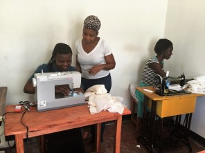 Stacey Scott, center, teaches Tanzanian women how to make western-style clothing in a converted room at African Integrative Medicine, where Scott is executive director. (contributed)