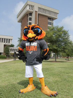 Curtiss, Auburn University at Montgomery's Warhawk mascot, poses before the school's iconic 10-story library on the campus in east Montgomery, Montgomery County. The mascot is named for the World War II-era Curtiss P-40 fighter plane. Prior to 2011, AUM's mascot was the Senators. (From Encyclopedia of Alabama, courtesy of Frank C. Williams of Auburn University at Montgomery)