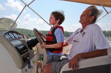 "Calvin Smith takes the wheel from his grandfather, David ""Bama"" Smith, on Logan Martin Lake. (Meg McKinney/Shorelines)"