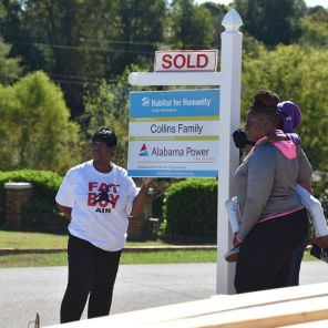The Collins family stand in front of their new home in Pleasant Grove. (Dennis Washington)