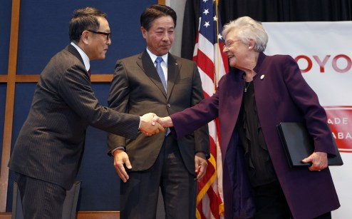 Gov. Kay Ivey shakes hands with Toyota President Akio Toyoda while Mazda President Masamichi Kogai looks on during an announcement ceremony for the companies' Alabama auto plant. (Hal Yeager/Governor's Office)
