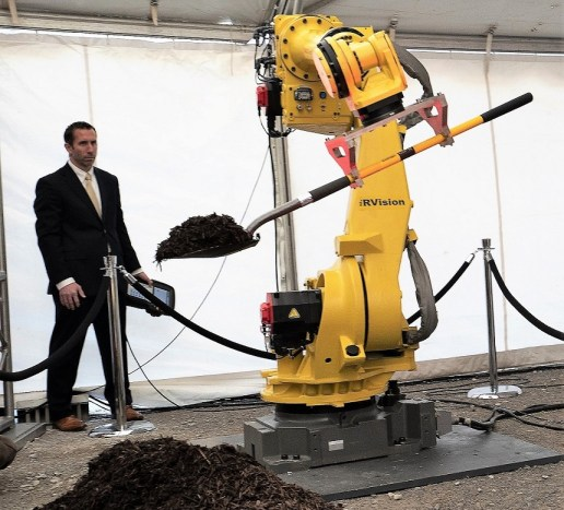 An industrial robot turns the first shovel of dirt at the 2018 groundbreaking ceremony for the $1.6 billion Mazda Toyota Manufacturing USA assembly plant in Huntsville. (Hal Yeager/Governor's Office)