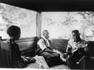 "Zora Neale Hurston interviews musicians Rochelle French and Gabriel Brown in this 1935 photo by musicologist Alan Lomax, taken in Eatonville, Florida. That same year, Hurston published her study of southern African-American folklore, ""Mules and Men."" (From Encyclopedia of Alabama, courtesy of Library of Congress)"