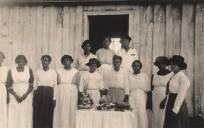 African-American women stand at a table of baked goods in Madison County, Alabama. The women are probably members of a local homemakers' club, c. 1915-17. (Alabama Department of Archives and History)