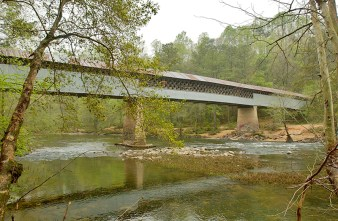 Swann Covered Bridge spans the Locust Fork of the Black Warrior River in Cleveland, central Blount County. The structure stretches 324 feet, and is one of three remaining covered bridges in the county, along with Horton Mill Covered Bridge in Oneonta and Easley Covered Bridge in Rosa. (From Encyclopedia of Alabama, courtesy of The Birmingham News, photograph by Philip Barr)
