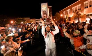 Anfernee McLemore carries the Midwest Regional Championship Trophy as the Auburn men's basketball team returns to Auburn after advancing to the Final Four. (Todd Van Emst/AU Athletics)