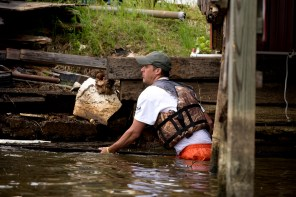 A Renew Our Rivers volunteer works to remove debris from the water. (Nik Layman/Alabama NewsCenter)