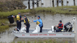 A Renew Our Rivers volunteer cleanup crew works to remove trash and debris from the water. (file)
