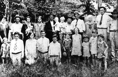 """In a photograph taken at a family reunion, c. 1925, young Hiram """"Hank"""" Williams stands, far left, in front of his mother, Lillie Williams. (From Encyclopedia of Alabama, courtesy of Hank Williams Boyhood Home/Museum)"""