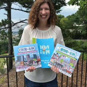 Ashley holds all three of her books, two of which are coloring books. (Keisa Sharpe)
