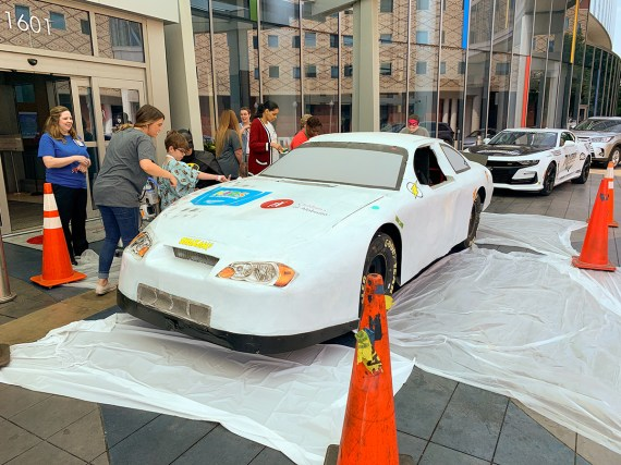 Patients at Children's of Alabama paint a race car from Talladega Superspeedway outside the hospital Friday morning. (Dennis Washington / Alabama NewsCenter)