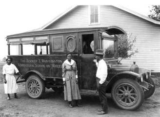 "Tuskegee agricultural science pioneer George Washington Carver developed the ""Movable School,"" a wagon and later a truck that brought new tools and crops to farmers who could not travel to Tuskegee for instruction. The staff of three included, from left, a home agent, a registered nurse, and a farm demonstration agent. (From Encyclopedia of Alabama, courtesy of the National Archives and Records Administration)"