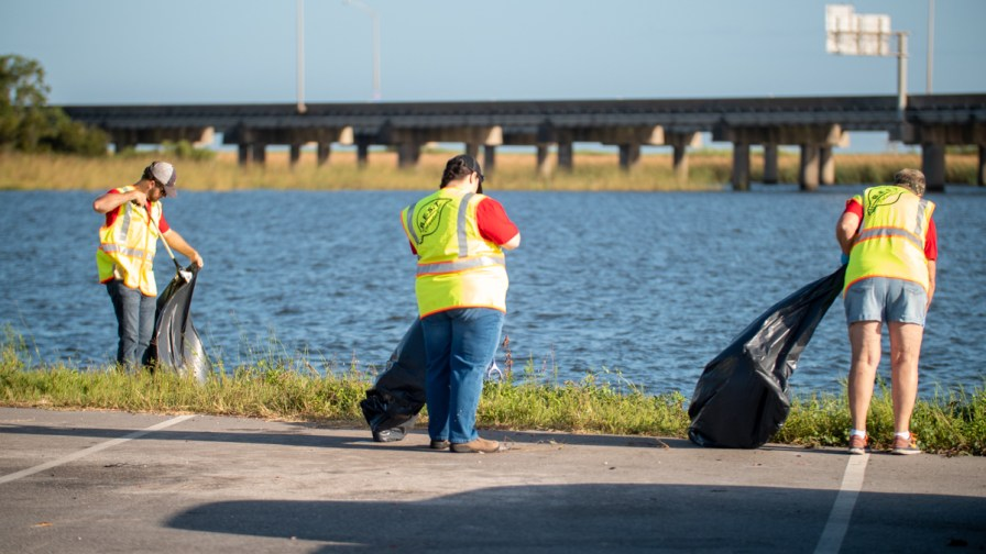 Employees from Alabama Power clean up areas around the Mobile Bay Causeway. (Dennis Washington / Alabama NewsCenter)