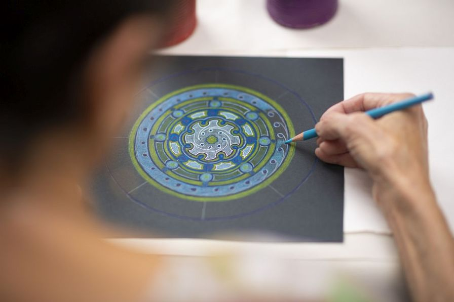 Applying blue pencil to black paper, Cook is painstaking in her work. (Phil Free/Alabama NewsCenter)