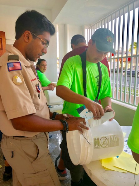 Shawn Goyal, left, works with Scouts in Puerto Rico to assemble Uzima water filters to distribute to families without clean water. (contributed)