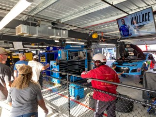 Fans watch as crew members work on the No. 43 car driven by Mobile native Bubba Wallace. (Dennis Washington / Alabama NewsCenter)