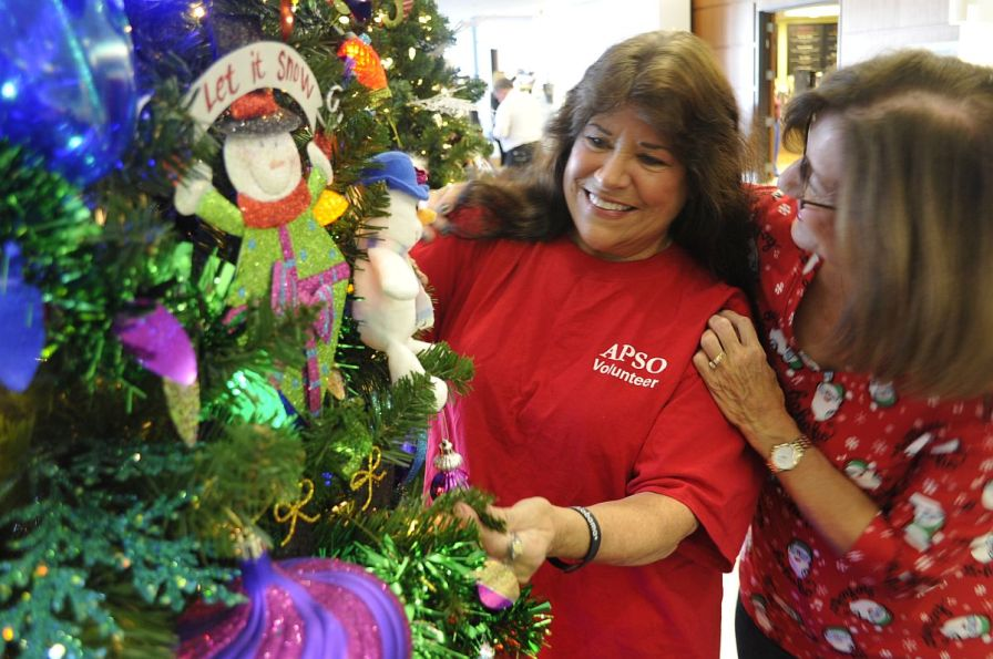 Alabama Power retiree DeArman (right) gets in the holiday spirit with Daly as they add pops of color to the Santa Claus tree. (Karim Shamsi-Basha/Alabama NewsCenter)