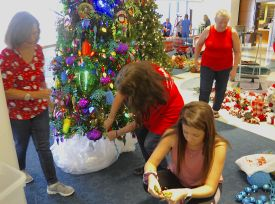 There was a flurry of activity as volunteers eagerly trimmed Christmas trees. (Karim Shamsi-Basha/Alabama NewsCenter)