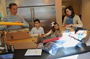 Ashley Seligson with husband Alex and children Braxton and Brooklyn, prepare gifts for the homeless they will serve during the holidays. (Karim Shamsi-Basha / Alabama NewsCenter)