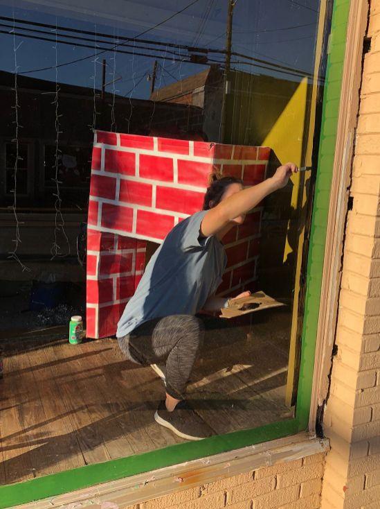A Gaston APSO member paints an empty storefront window. (Karen White / Alabama NewsCenter)