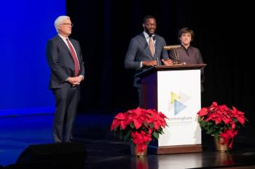 Birmingham Mayor Randall Woodfin, center, speaks as incoming BBA Chairman Jim Gorrie and departing BBA Chairwoman Nancy Goedecke look on. (BBA)