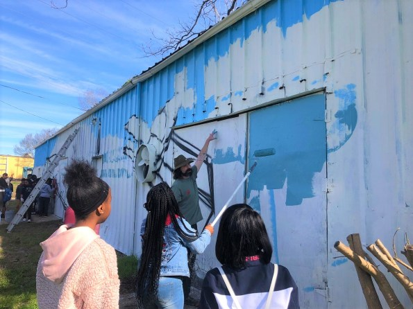 Students from the R.B. Hudson High School STEAM Academy are working with the nonprofit ArtsRevive group to create a mural on the side of a building owned by Cougar Oil in Selma. (Michael Jordan/Alabama NewsCenter)