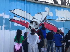 Students from the R.B. Hudson STEAM Academy use a wall fan as the propeller for a vintage airplane in the mural they're creating on Cougar Oil property in Selma. (Michael Jordan/Alabama NewsCenter)