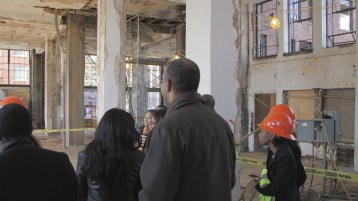 A group tours the interior of the American Life building, which is being transformed into an apartment building. (Michael Tomberlin/Alabama NewsCenter)