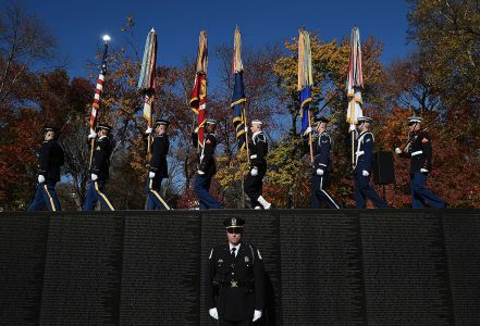 "Members of the ""Old Guard"" present the colors along the top of the Vietnam Memorial Wall during a Veterans Day ceremony at the Vietnam Veterans Memorial in Washington, D.C. (Photo by Win McNamee/Getty Images)"