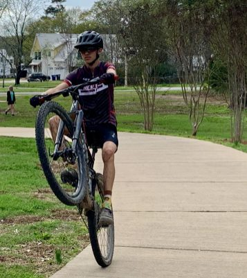 A freewheeling teen exercises with his bike in Civitan Park. (Donna Cope/Alabama NewsCenter)